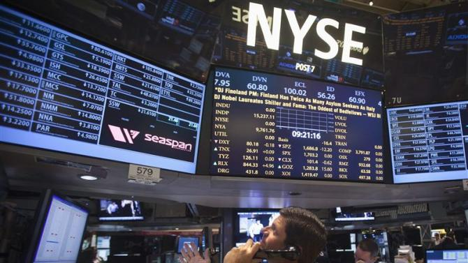 A trader looks up at a screen on the floor of the New York Stock Exchange at the market open in New York