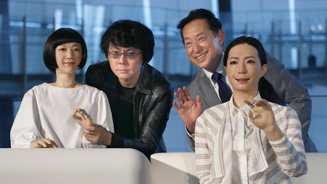 Japanese android expert Hiroshi Ishiguro, second left, and National Museum of Emerging Science and Innovation Miraikan Chief Executive Director Mamoru Mohri, second right, pose with a female-announcer robot called Otonaroid, right, and a girl robot called Kodomoroid during a press unveiling of the museum's new guides in Tokyo Tuesday, June 24, 2014. The latest creations from Osaka University Prof. Ishiguro are the Otonaroid, the Kodomoroid and Telenoid, a hairless mannequin head with pointed arms that serves as a cuddly companion. The robots with silicon skin and artificial muscles were shown to reporters at Miraikan museum on Tuesday. (AP Photo/Shizuo Kambayashi)