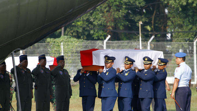 Indonesian air military personnel carry the coffin of a victim in an Indonesian air force plane crash at Halim Perdanakusuma air base in Jakarta, Indonesia, Friday, June 22, 2012. Rescuers Friday resumed searching burned-out houses struck by the plane that crashed into the military housing complex and ignited a huge fireball in the capital. (AP Photo/Achmad Ibrahim)
