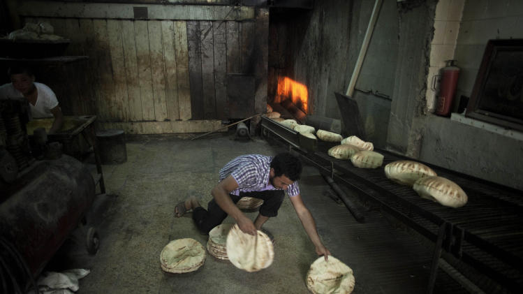 In this Saturday, Sept. 22, 2012 photo a Syrian man works at a bakery in the in Saif Al Dawla neighborhood of Aleppo, Syria, Friday, Sept. 21, 2012. (AP Photo/ Manu Brabo)