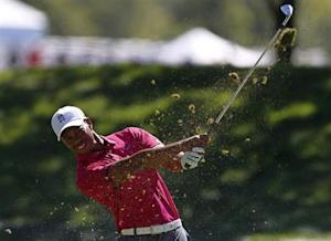 Woods of the U.S. watches his approach shot on the first hole during the third round of the BMW Championship golf tournament at the Conway Farms Golf Club in Lake Forest