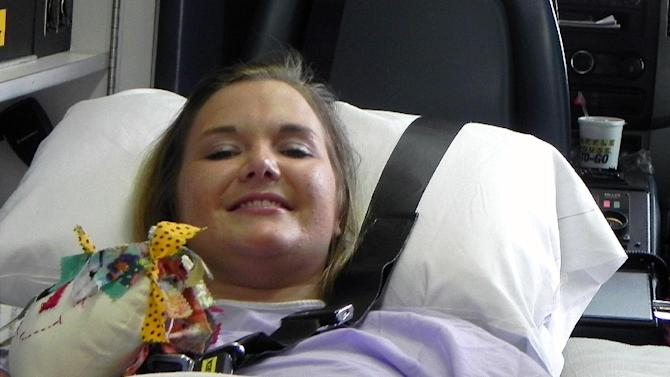 In this Monday, July 2, 2012 file photo provided by Andy Copeland, Aimee Copeland smiles as she leaves a hospital in Augusta Ga., headed for an inpatient rehabilitation clinic. On Wednesday, Aug. 22, 2012, after more than three months in the hospital and a rehabilitation clinic, Copeland, who survived a rare fleshing-eating disease but had both her hands, her left leg and her right foot amputated, returned home to a family dinner and a wheelchair-accessible house now equipped with an exercise room and private elevator. (AP Photo/Courtesy Andy Copeland, File)