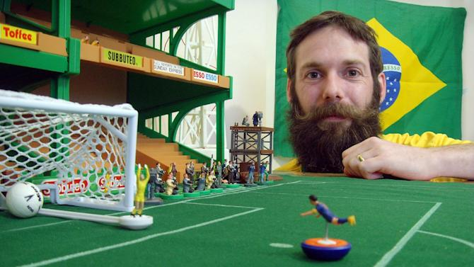 British artist Terry Lee, who lives in Brazil, poses with some of his football figurines in his studio outside Rio de Janeiro on June 19, 2014