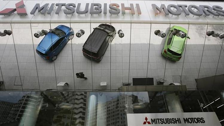 Mitsubishi Motors Corp's vehicles and a passer-by are reflected on an external wall at the company headquarters in Tokyo May 23, 2013.