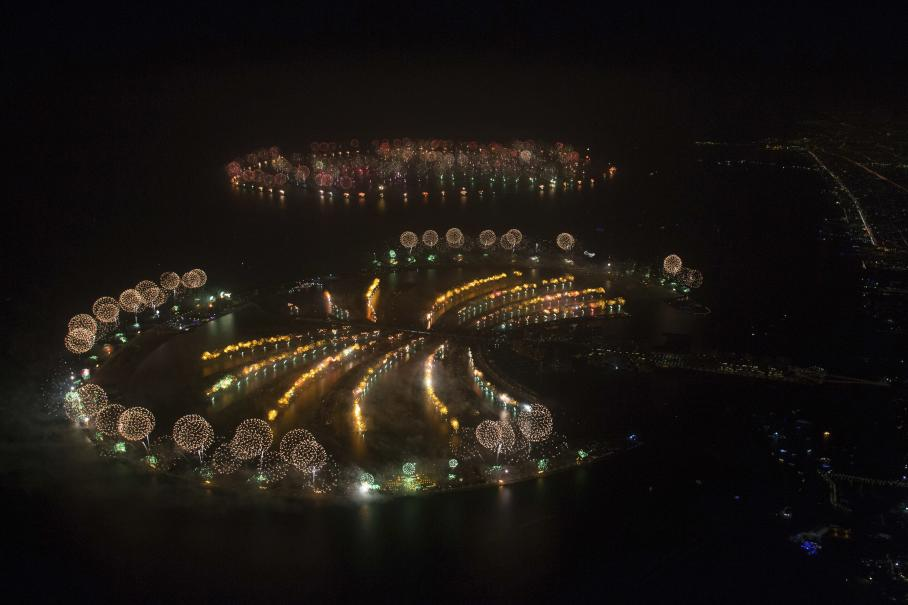 "In this photo provided by Dubai World Record 2014, fireworks explode over Palm Jumeirah Island, front, and World Islands, rear, to celebrate the New Year on Wednesday, Jan. 1, 2014 as the city attempts to breaks the Guinness World Record for the ""Largest Firework Display."" (AP Photo/Dubai World Record 2014, Simon Brooke-Webb)"