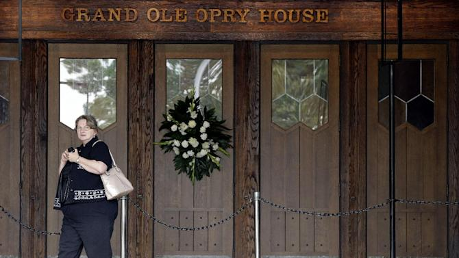 Jean Tanner, of Madison, Ga., walks past a wreath hung on a door at the Grand Ole Opry House in memory of country music star George Jones on Wednesday, May 1, 2013, in Nashville, Tenn. The Opry House is where the funeral for Jones will be held Thursday, May 2. Jones, one of country music's biggest stars who had No. 1 hits in four separate decades, died April 26.  (AP Photo/Mark Humphrey)