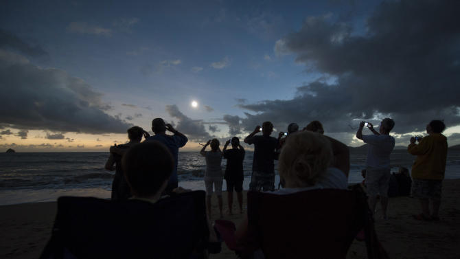 In this photo released by Tourism Queensland, people gather on Palm Cove beach in Queensland state, Australia, to watch a total solar eclipse Wednesday, Nov. 14, 2012. Starting just after dawn, the eclipse cast its 150-kilometer (95-mile) shadow in Australia's Northern Territory, crossed the northeast tip of the country and was swooping east across the South Pacific, where no islands are in its direct path. (AP Photo/Tourism Queensland, Murray Anderson-Clemence) EDITORIAL USE ONLY
