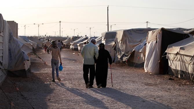 Syrian elderly refugees walk at the Zaatari refugee camp, near the Syrian border, in Mafraq, Jordan, Monday, April 29, 2013. Jordan's economy is ailing and some lawmakers have expressed concerns over the rising numbers of Syrian refugees in the resource-poor kingdom. (AP Photo/Mohammad Hannon)