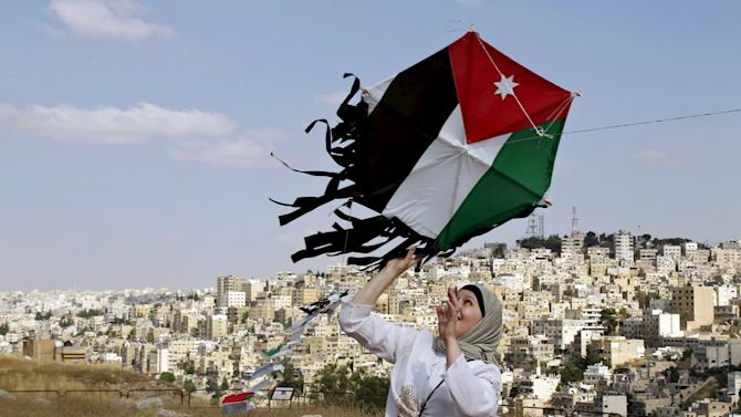 Woman prepares to fly a kite decorated with the Jordanian national flag during an event to celebrate Jordan's Independence Day at the Amman Citadel