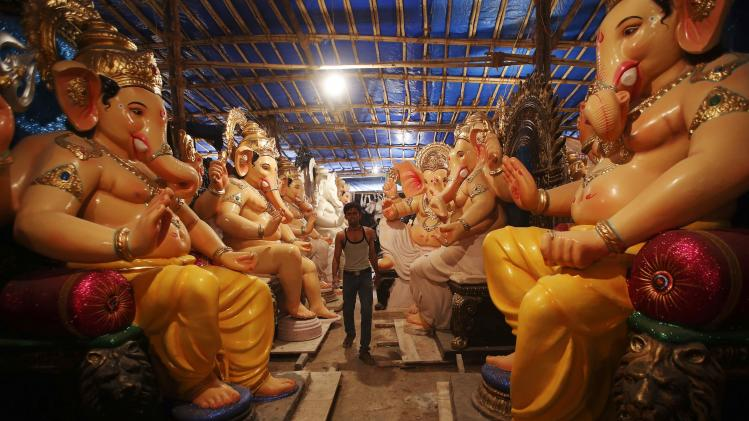 An artisan walks past the idols of Hindu elephant god Ganesh, the deity of prosperity, kept inside a workshop in Mumbai