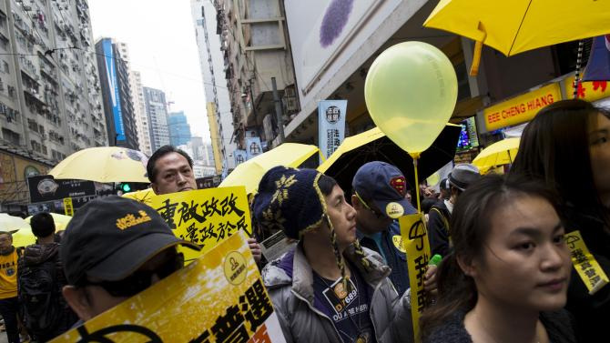 "Pro-democracy protesters hold up yellow umbrellas, symbols of the Occupy Central movement, and banners reading ""I want real universal suffrage"" during a march in the streets to demand universal suffrage in Hong Kong"