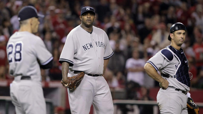New York Yankees starting pitcher CC Sabathia, center, manager Joe Girardi, left, and catcher Jorge Posada watch as umpires confer in the sixth inning of a baseball game against the Los Angeles Angels in Anaheim, Calif., Saturday, Sept. 10, 2011. (AP Photo/Jae Hong)