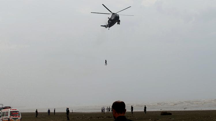 A Pakistan Navy helicopter evacuates a recovered body of a victim who drowned over Clifton beach in Karachi, Pakistan, Aug. 1, 2014. Pakistan's navy has recovered dozens of bodies, drowned earlier this week when strong winds swept through the country's southern beaches near the city of Karachi, a spokesman said Friday. (AP Photo/Fareed Khan)