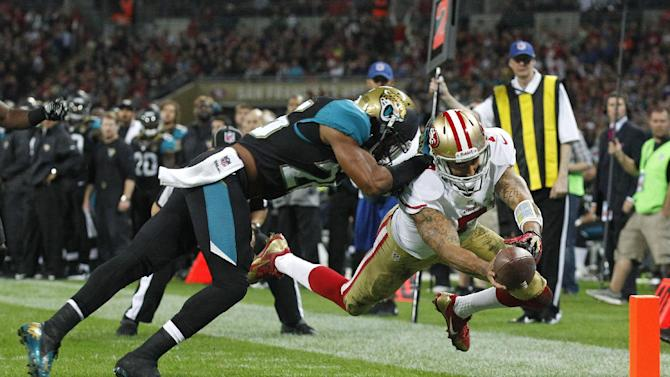 San Francisco 49ers quarterback Colin Kaepernick (7), right, dives to score a touchdown despite the challenge of Jacksonville Jaguars free safety Josh Evans (26) during the NFL football game between San Francisco 49ers and Jacksonville Jaguars at Wembley Stadium in London, Sunday, Oct. 27, 2013