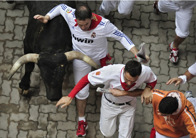 Revelers run beside one Miura ranch bull during the fourth running of the bulls at the San Fermin fiestas in Pamplona, northern Spain, Sunday, July 10, 2011. (AP Photo/Alvaro Barrientos)