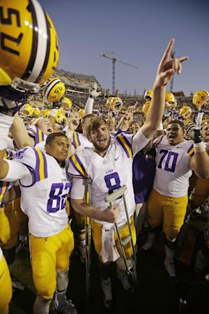 LSU quarterback Zach Mettenberger (8), wide receiver James Wright (82) and offensive tackle La'el Collins (70) celebrate their31-27 victory over Arkansas in an NCAA college football game in Baton Rouge, La., Friday, Nov. 29, 2013. (AP Photo/Bill Haber)
