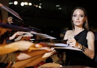 "Hollywood actress Angelina Jolie gives her autograph to fans at the Japan premiere of her partner Brad Pitt's movie ""World War Z"" in Tokyo July 29, 2013. REUTERS/Issei Kato/Files"