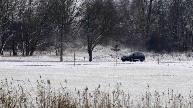 A car moves through a snow-covered landscape in Wustermark