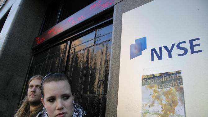 """A woman looks at a flyer reading """"Capitalism Crashes"""" attached to the NYSE Euronext stock exchange in Amsterdam, Netherlands, Saturday Oct. 15, 2011, during a demonstration in support of the Occupy Wall Street movement. Demonstrators in hundreds of cities all over the world protested against corporate power and the banking system. (AP Photo/Peter Dejong)"""