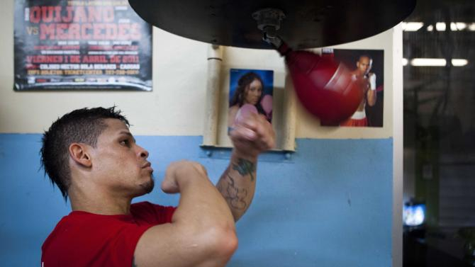 """Boxer Orlando Cruz hits the speed bag while posing for pictures after a training session at a public gym in San Juan, Puerto Rico, Thursday, Oct. 4, 2012. Describing himself as """"a proud gay man"""", Puerto Rican featherweight Orlando Cruz on Thursday became what is believed to be the first pro boxer to come out as openly homosexual while still competing. (AP Photo/Dennis M. Rivera Pichardo)"""