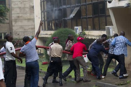 People gather to pull a hose after a fire broke out at the headquarters of the Nigeria Football Federation in Abuja