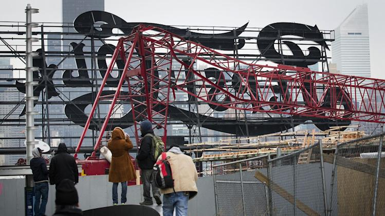 "Onlookers observe a mangled crane at the construction site in the Queens borough of New York where it collapsed, Wednesday, Jan. 9, 2013 behind a big neon ""Pepsi Cola"" sign, a local landmark. The Fire Department of New York says the 200-foot crane collapsed onto a building under construction, injuring seven people, three of them seriously. (AP Photo/John Minchillo)"