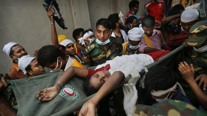 A Bangladeshi woman survivor is carried from the rubble by rescuers at the site of a building that collapsed Wednesday in Savar, near Dhaka, Bangladesh, Thursday, April 25, 2013. By Thursday, the death toll reached at least 194 people as rescuers continued to search for injured and missing, after a huge section of an eight-story building that housed several garment factories splintered into a pile of concrete.(AP Photo/Kevin Frayer)