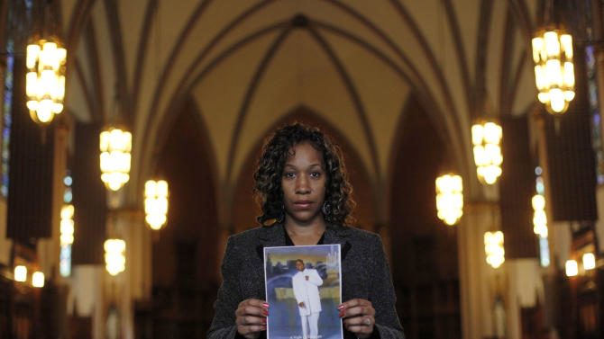Pam Bosley stands inside the St. Sabina Catholic Church  with a photograph of her son, Terrell, who was gunned down in 2006. Wednesday, March 9, 2011 in Chicago. Gov. Pat Quinn abolished the death penalty Wednesday, more than a decade after the state imposed a moratorium on executions. Bosley said no one is in custody in her son's death, but whoever killed him does not deserve to live.(AP Photo/Charles Rex Arbogast)