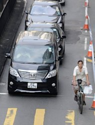 A cyclist makes his way through traffic in Hong Kong. The majority of two-wheelers are men on rickety contraptions with improvised front and back crates, carrying everything from gas cannisters to live fish