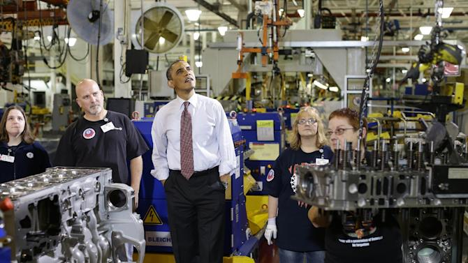 President Barack Obama watches workers during a visit to the heavy duty engines line at the Daimler Detroit Diesel plant in Redford, Mich., Monday, Dec. 10, 2012. (AP Photo/Charles Dharapak)