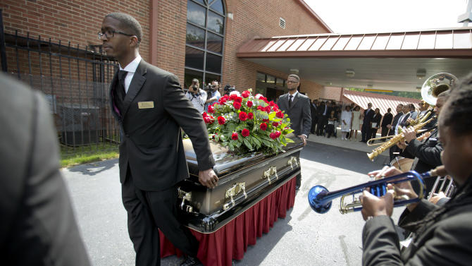 """The casket of Chris Kelly of the rap duo Kris Kross, is rolled to a waiting hearse following his funeral service, Thursday, May 9, 2013, in Atlanta. The 34-year-old Kelly was found dead May 1 of a suspected drug overdose. Kriss Kross was introduced to the music world in 1992 by music producer and rapper Jermaine Dupri after he discovered the pair at a mall in southwest Atlanta. Kelly performed alongside Chris Smith, who known as """"Daddy Mac."""" (AP Photo/David Goldman)"""