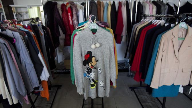 """FILE - In this Dec. 9, 2011 file photo, a Minnie Mouse sweater and other clothing items are displayed for sale at a shop in Pyongyang, North Korea. Outside, in a world awash in Disney and hip hop, the changes may seem minor. But in North Korea, they represent a sea change for this country built on a philosophy of """"juche,"""" or self-reliance, where shutting out the West and keeping information on a """"need to know basis"""" was for decades a state policy. (AP Photo/David Guttenfelder, File)"""