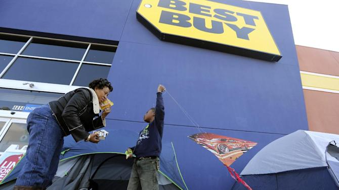 FILE -In this Monday, Nov. 19, 2012, file photo, Denise Smith-Lad, left, asks her grandson Jordan Smith, 6, what he would like to eat as they camp in front of a Best Buy store in Cockrell Hill, Texas. Best Buy Co. reported another dismal quarter on Tuesday, Nov. 20, 2012, recording a loss in the third quarter, hurt by a continued sales slump and charges related to restructuring. Shares fell 5 percent in premarket trading.  The electronics chain is struggling to reverse a years long decline in its business as competition from online stores and discounters increases, and consumers' tastes shift from more profitable items like TVs and desktop computers toward less profitable smartphones and tablets.  (AP Photo/LM Otero)