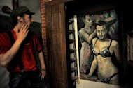 "A visitor looks at an artwork representing Russia's President Vladimir Putin and Russian Prime Minister Dmitry Medvedev by Russian artist Konstantin Altunin during the ""Leaders"" exhibition in St. Petersburg on August 21, 2013. Altunin said Thursday he has fled to France and is applying for asylum"