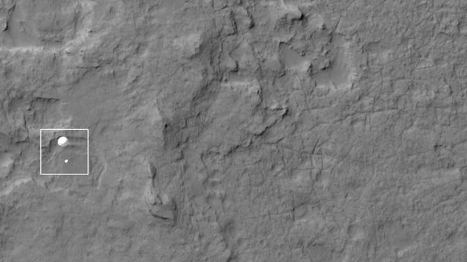 In this photo released by NASA/JPL-Caltech/Univ. of Arizona, NASA's Curiosity rover and its parachute, left, descend to the Martian surface on Sunday, Aug. 5, 2012. The high-resolution Imaging Science Experiment (HiRISE) camera captured this image of Curiosity while the orbiter was listening to transmissions from the rover. (AP Photo/NASA/JPL-Caltech/Univ. of Arizona)