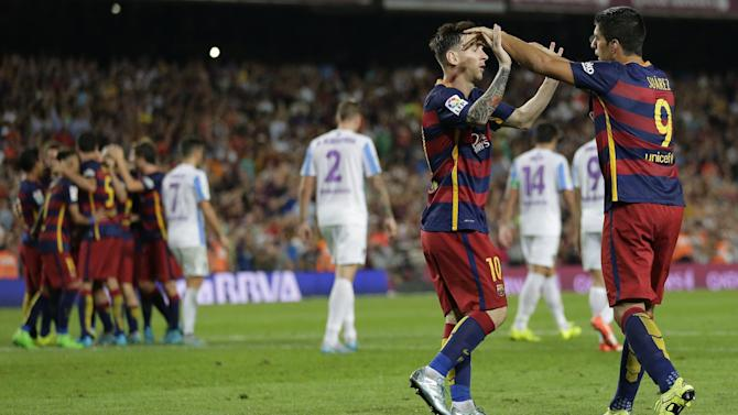 FC Barcelona's Lionel Messi, from Argentina, second right, celebrates with his teammate Luis Suarez, from Uruguay, after Thomas Vermaelen scored against Malaga during a Spanish La Liga soccer match at the Camp Nou stadium in Barcelona, Spain, Saturday, Aug. 29, 2015. (AP Photo/Manu Fernandez)
