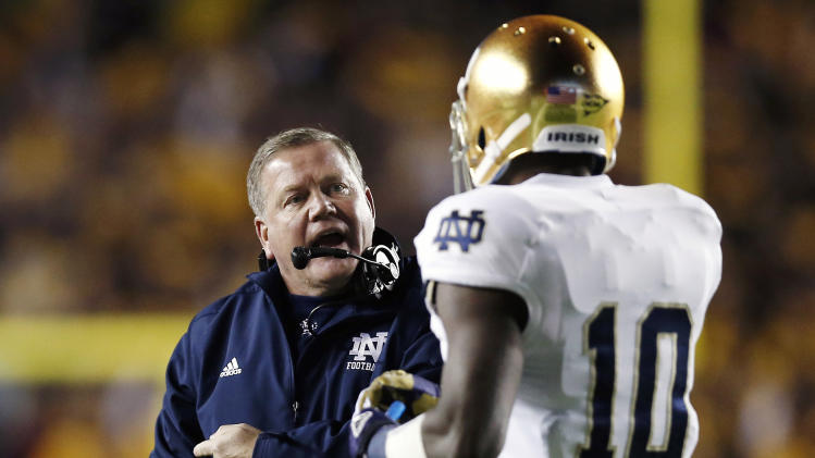 Notre Dame head coach Brian Kelly talks with wide receiver DaVaris Daniels during the first half of an NCAA college football game against Boston College in Boston Saturday, Nov. 10, 2012. (AP Photo/Winslow Townson)