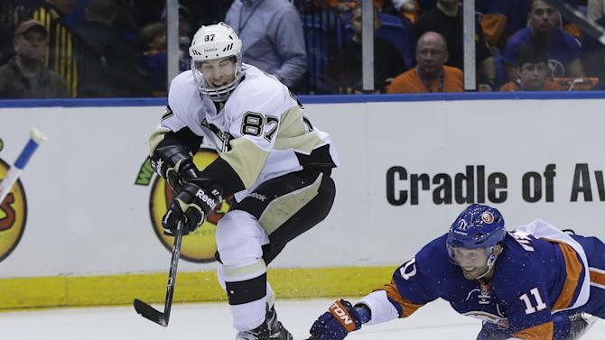 Pittsburgh Penguins' Sidney Crosby, left, passes past New York Islanders' Lubomir Visnovsky during the first period of Game 3 of an NHL hockey Stanley Cup first-round playoff series, Sunday, May 5, 2013, in Uniondale, N.Y. (AP Photo/Seth Wenig)