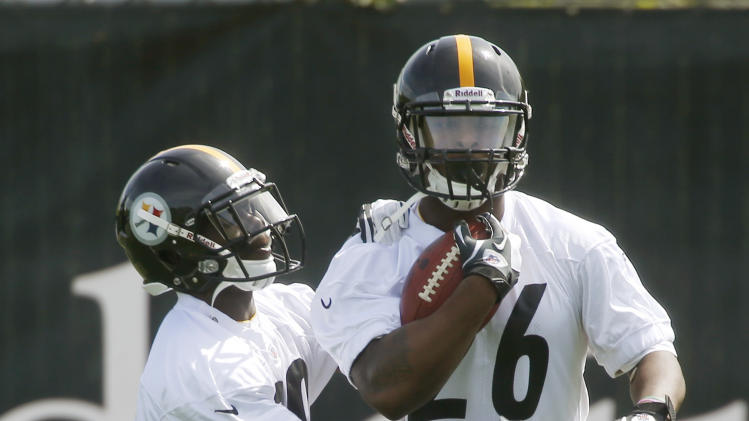 Pittsburgh Steelers second round draft pick running back Le'Veon Bell, right, gets poked at by free agent running back Curtis McNeal from Southern California, during ball retention drills at the NFL football rookie minicamp on Friday, May 3, 2013 in Pittsburgh. (AP Photo/Keith Srakocic)