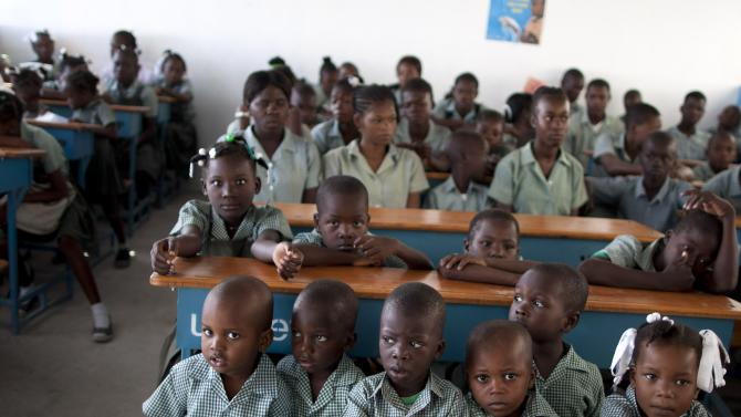 "In this Friday, May 25, 2012 photo, students crowd together at desks in their classroom at LaPorte Elementary School in Port-au-Prince, Haiti. Amid the horrors of Haiti's 2010 earthquake lay a promise of renewal. With the United States taking the lead, international donors pledged billions of dollars to help it ""build back better,"" breaking its cycle of dependency. Yet 2 1/2 years later, the fruits of an ambitious $1.8 billion U.S. reconstruction promise are hard to find. (AP Photo/Dieu Nalio Chery)"