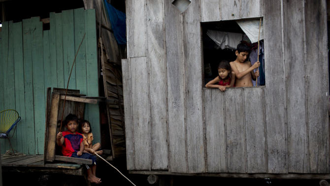 "In this April 19, 2015 photo, children fish from their home sitting just above the water line in the Belen neighborhood of Iquitos, a community in Peru's Amazon nicknamed ""Venice of the Jungle."" Along with the homes, the community boasts a Roman Catholic and various evangelical churches. It even has bordellos, discotheques, lumber mills and casinos. Many inhabitants work in a market in a nearby area that never floods, selling shad and other fish they catch in the river. (AP Photo/Rodrigo Abd)"