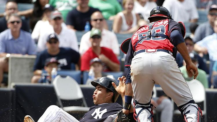 New York Yankees' Ramon Flores, left, scores as he slides past Atlanta Braves catcher Christian Bethancourt (58) in the fifth inning of a spring exhibition baseball game in Tampa, Fla., Sunday, March 16, 2014. Bethancourt lost control of the ball in the play