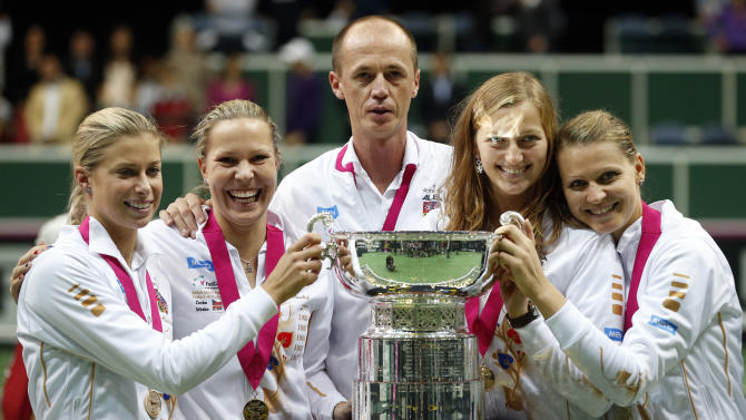Czech Republic's team, left to right, Andrea Hlavackova, Lucie Hradecka, Petr Pala, Petra Kvitova and Lucie Safarova celebrate with trophy after defeating Serbia in the  final of the Fed Cup tennis tournament in Prague, Czech Republic, Sunday, Nov. 4, 2012. (AP Photo/Petr David Josek)