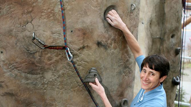 FILE - This March 22, 2006 file photo shows Recreational Equipment, Inc. (REI) CEO Sally Jewell climbing the 65-foot rock climbing pinnacle at REI's Seattle flagship store. She doesn't wear a cowboy hat favored by traditional picks for Secretary of the Interior. Jewell prefers fleece and Gore-Tex jackets and wears a safety helmet when she needs it for scaling cliffs, skiing or kayaking. (AP Photo/Scott Cohen, File)