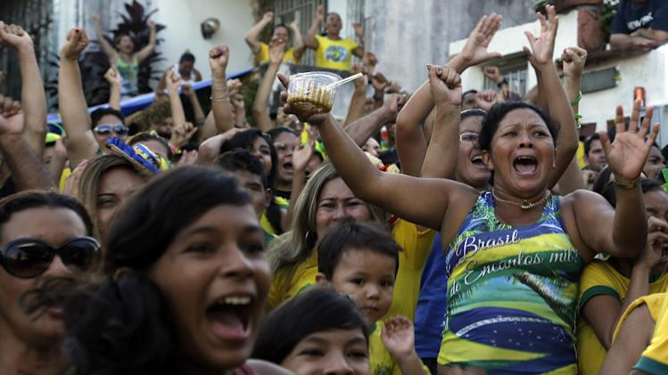 Soccer fans cheer after Brazil scored against Cameroon while watching the match on a big screen in Manaus, Brazil, Monday, June 23, 2014. Brazil's Neymar scored twice in the first half to lead Brazil to a 4-1 win over Cameroon on Monday, helping the hosts secure a spot in the second round of the soccer World Cup