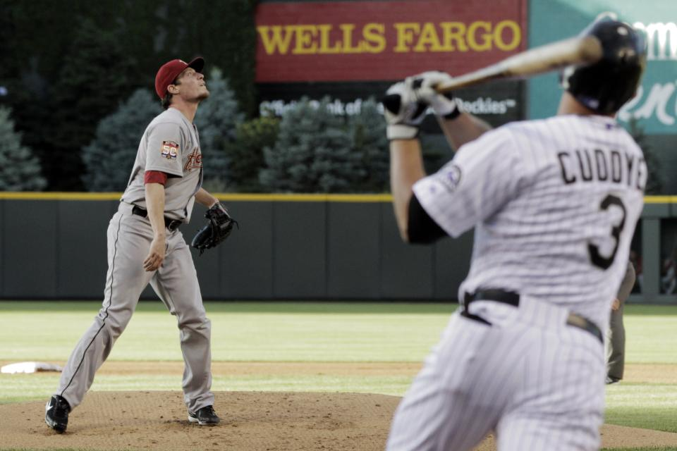 Houston Astros starting pitcher Lucas Harrell, left, watches Colorado Rockies' Michael Cuddyer's grand slam in the first inning of a baseball game, Wednesday, May 30, 2012, in Denver. (AP Photo/Joe Mahoney)