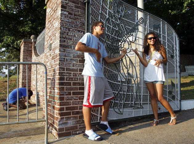 FILE -- This Aug. 2010 photo shows fans posing at the gates of Graceland, Elvis Presley's home in Memphis, Tenn. Graceland opened for tours on June 7, 1982. They sold out all 3,024 tickets on the first day and didn't look back, forever changing the Memphis tourist landscape while keeping Elvis and his legend alive.(AP Photo/Mark Humphrey)