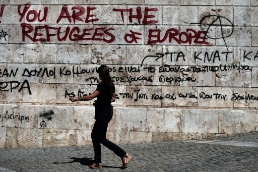 "<p>A woman walks past graffiti outside the Athens Academy on September 20. The ""troika"" of international creditors called time out Friday on lengthy bailout negotiations with the Greek government, deciding on a pause for about a week.</p>"