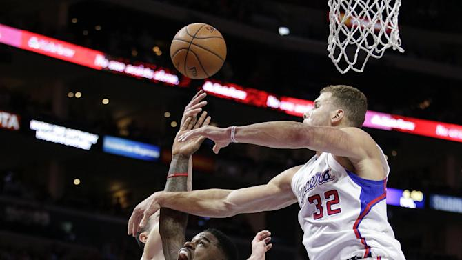Toronto Raptors' Amir Johnson, center, is defended by Los Angeles Clippers' Blake Griffin, right, and J.J. Redick during the second half of an NBA basketball game Saturday, Dec. 27, 2014, in Los Angeles. The Raptors won 110-98. (AP Photo/Jae C. Hong)