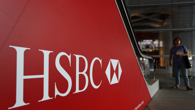 FILE -- In a July 30, 2012 file photo people walk past a logo of HSBC headquarters in Hong Kong .  HSBC, the British banking giant, will pay $1.9 billion to settle a money-laundering probe by federal and state authorities in the United States, a law enforcement official said Monday Dec. 10, 2012.  (AP Photo/Vincent Yu, file)